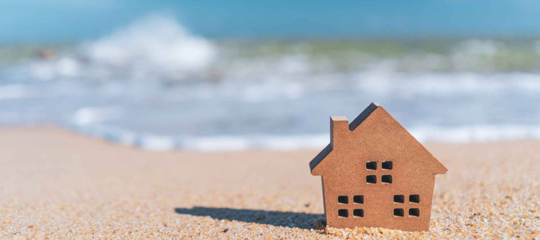 Small home model on sand beach with blue sky and white clouds background. Copy space of family lifestyle and business real estate concept. Vintage tone filter effect color style.