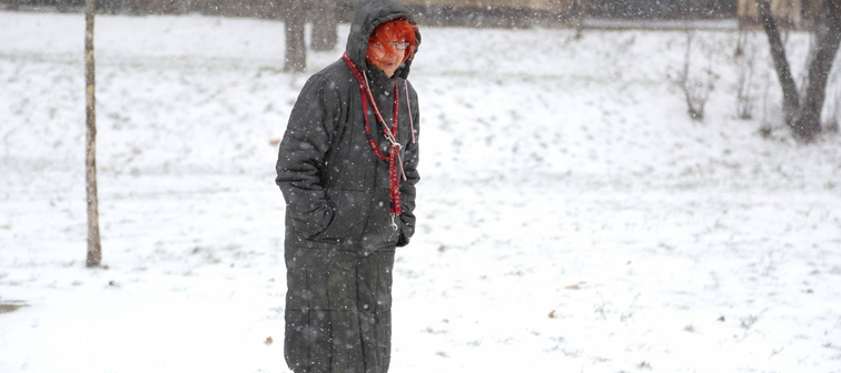 Senior woman walking on blizzard day in park. Weather changes concept.