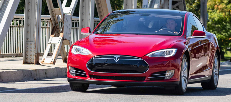 LONDON, CANADA - September 19, 2019: Man driving Tesla Model S across a bridge on a sunny day in London, Ontario.