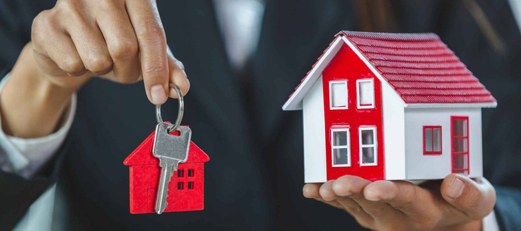 Real estate agent with a red house key ring and red house on the hands of investors Real estate concept, mortgage, home agent, contract to buy a house, sell or rent.