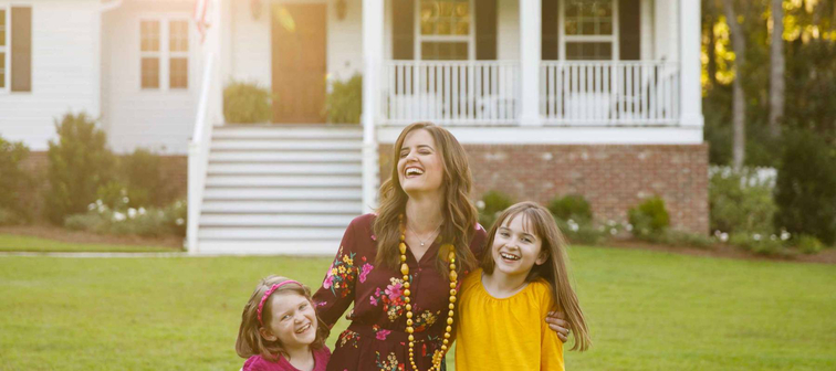 Mom and Two Daughters Laughing and Hugging Outside their New Farmhouse Home
