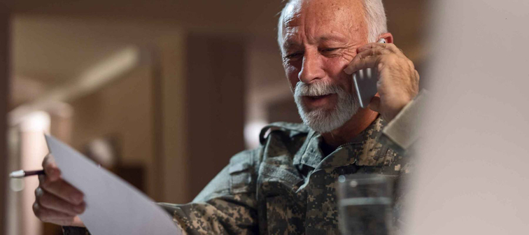 Happy mature veteran in army uniform communicating on cell phone while doing paperwork in the office.