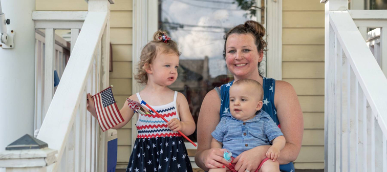 Mom and kids on front porch of their home on Fourth of July
